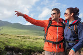 Couple wearing rain jackets and sunglasses admiring the scenery with man pointing — Stock Photo