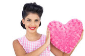 Lovely black hair model holding a pink heart shaped pillow — Stock Photo