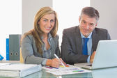 Two concentrated business people smiling at camera trying to understand figures — Stock Photo