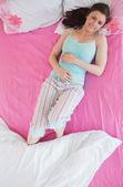 Брюнетка в пижаме, лежа на кровати и улыбка на камеру — Стоковое фото