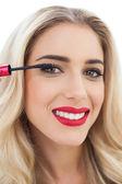 Smiling blonde model in blue dress applying mascara — Stock Photo