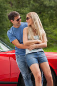 Smiling couple hugging and leaning against cabriolet — Stock Photo