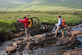 Couple crossing a river holding their bikes — Stok fotoğraf