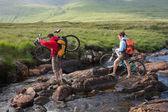 çift bisiklet tutan bir nehir geçiş — Stok fotoğraf