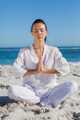 Woman practicing yoga at the beach — Stock Photo