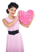 Playful black hair model holding a pink heart shaped pillow — Stock Photo