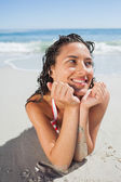 Close up view of smiling woman lying down on beach — Stock Photo