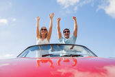 Crazy couple standing in red cabriolet — Stock Photo