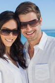 Happy couple wearing sunglasses and smiling at camera — Stock Photo