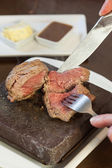 Medium rare steak sizzling on hot stone plate being sliced — Stock Photo