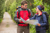 Fit couple going on a hike together looking at map — Stock Photo