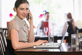 Businesswoman calling on phone using laptop — Stock Photo