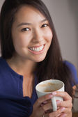 Happy asian woman holding mug of coffee looking at camera — Stock Photo