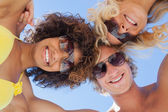 Low angle view of friends on beach wearing sunglasses — Stock Photo