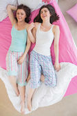 Close friends in pajamas lying on bed and laughing — Stock Photo