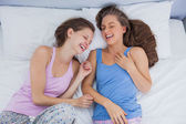 Girls wearing pajamas lying in bed and laughing — Stock Photo