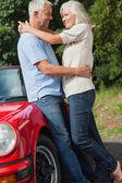 Coppia matura felice abbracciando contro loro cabriolet rossa — Foto Stock