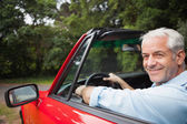 Smiling handsome man driving red cabriolet — Stock Photo