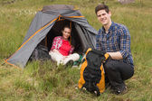 Smiling man packing backpack while girlfriend sits in tent — Zdjęcie stockowe