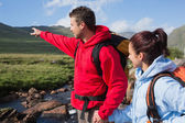 Couple standing at edge of river on a hike with man pointing — Stock Photo