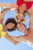 Low angle view of happy friends on beach — Stock Photo