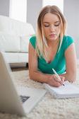 Concentreren vrouw liggen op verdieping haar huiswerk met behulp van laptop — Stockfoto