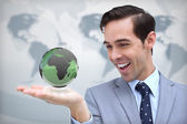 Content businessman admiring a green globe — Stock Photo