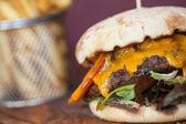 食欲をそそるチーズバーガーにクローズ アップ — ストック写真