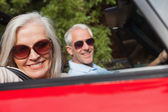 Side view of cheerful mature couple driving red cabriolet — Stock Photo