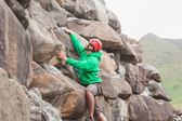Fit man scaling a large rock face — Stock Photo