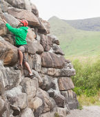Focused man ascending a large rock face — Stock Photo