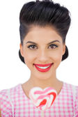 Happy black hair model holding a heart shaped lollipop — Stock Photo