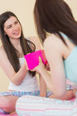 Happy girl in pajamas receiving a present from her friend — Stock Photo
