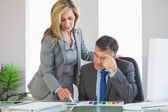 Frowning businesswoman explaining figures to a businessman — Stock Photo