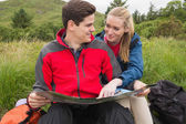 Smiling couple taking a break on a hike to look at map — Stockfoto
