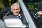 Content businessman driving expensive cabriolet — Stock Photo