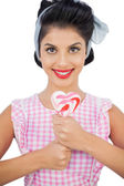 Cheerful black hair model holding a heart shaped lollipop — Stock Photo