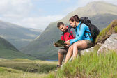 Couple taking a break after hiking uphill and reading map — Zdjęcie stockowe