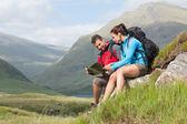 Paar eine pause nach dem wandern bergauf und reading anzeigen — Stockfoto