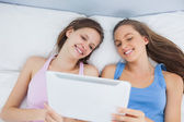 Friends looking at tablet and laughing — Stock Photo