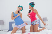 Girls in hair rollers singing with hairbrush — Stok fotoğraf