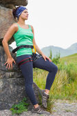 Attractive female rock climber leaning on rock face — Stock Photo