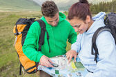 Couple sitting after hiking uphill and consulting map — ストック写真