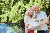 Smiling mature couple looking for direction — Stock Photo
