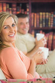 Happy couple drinking coffee sitting on a sofa — Stock Photo