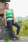 Attractive female rock climber leaning on rock face smiling at camera — Stock Photo
