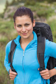 Smiling female hiker with backpack looking at camera — Stock Photo