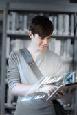 Focused student analysing graphs on his digital tablet — Stock Photo