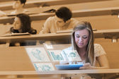 Pretty blonde student analysing graphs on her digital tablet — Stock Photo