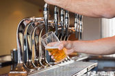 Mans hand pouring beer — Stock Photo